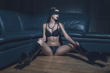 Sexy woman in blindfold and latex platform boots bite whip at night