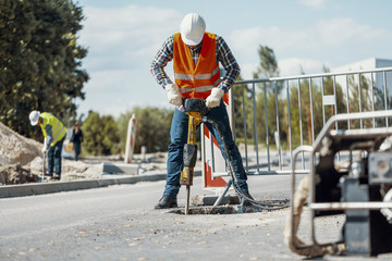 Worker in reflective vest with drill repairing street during roadworks