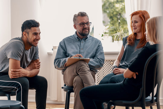 Smiling spanish man talking with friends during meeting for teenagers with therapist