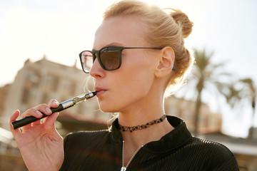 A girl smoking vape on Barceloneta beach in Barcelona