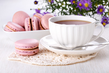 Cup of tea and pink macaroons - French cookies on white table. Teatime.