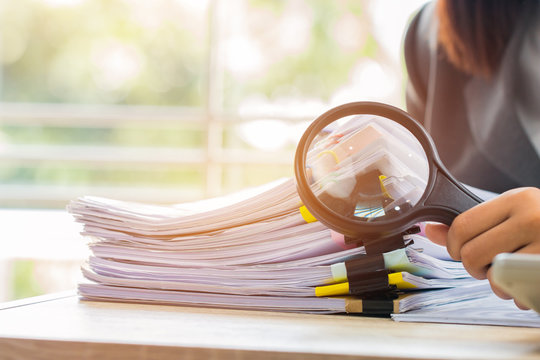 Asian Businessman use Magnifying glass scaning documents for checking investigate analytics and statistics. Stacks of paper files maketing document report in table office.