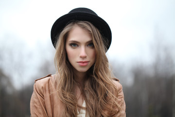 Pretty young woman in hipster hat outdoors, portrait