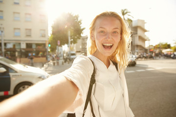 A girl making an emotional selfie at a crossroad in Barcelona