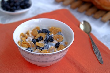 Summer breakfast, natural yoghurt with cornflakes and berries of edible honeysuckle
