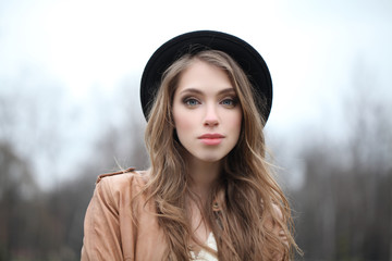 Attractive young woman in hipster hat outdoors, portrait