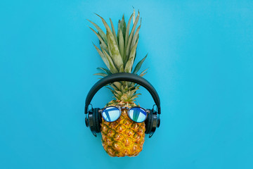 stylish pineapple in sunglasses and headphones on trendy blue paper background. summer flat lay. vacation and party concept. space for text. hipster holidays