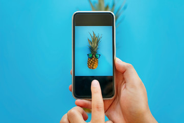 instagram fruit photo. hands holding phone and taking photo of pineapple in sunglasses on blue paper, trendy flat lay. stylish food photography. creative phone image