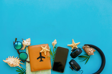 travel and wanderlust flat lay. planning summer vacation concept. passport, map, phone, sunglasses, headphones on blue trendy paper with shells. space for text. stylish creative image