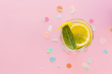 mojito cocktail drink on trendy pink paper background with confetti flat lay. fresh drink water with lemon and mint. space for text. summer holidays. vacation and party concept