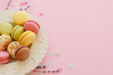 tasty colorful macarons in vintage plate on trendy pastel pink paper with lavender and confetti. space for text pink, yellow, green, white, brown macaroons. modern food photography