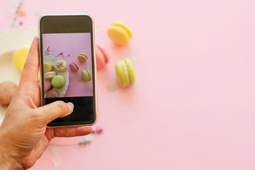 hand holding phone and taking photo of tasty colorful macarons in plate on trendy pastel pink paper flat lay. space for text. modern food photography concept. instagram photo workshop