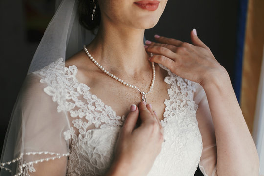 beautiful bride holding expensive silver necklace with pearls on neck. woman in white gown with lace floral ornaments, bridal morning preparations. stylish jewelry. boudoir photo