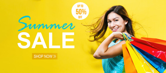 Summer sale with happy young woman holding shopping bags on a yellow background Wall mural