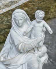 White stone statue of the virgin Mary carrying a baby