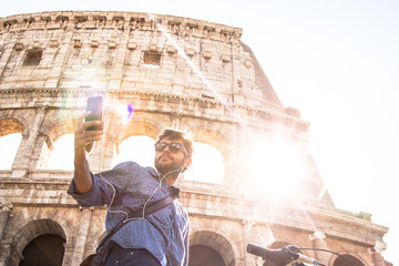 Young hipster man with bike at colosseum taking selfies pictures with smartphone in Rome city centre on sunny day