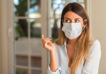 Beautiful young woman wearing contamination mask at home. Pollution and illness concept.