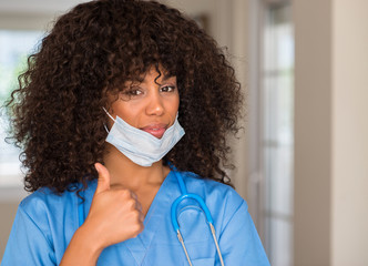 African american woman medical professional happy with big smile doing ok sign, thumb up with fingers, excellent sign