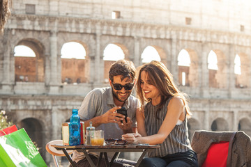 Happy young couple tourists using smartphone sitting at bar restaurant in front of colosseum in rome at sunset with coffee shopping bags smiling having fun texting browsing and sharing pictures