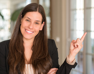 Young beautiful woman at home very happy pointing with hand and finger to the side