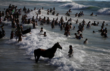 Palestinians swim to cool off in the Mediterranean Sea off the coast of Gaza City