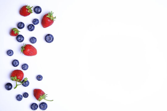 Bunch of fresh organic mixed berries, blueberry & strawberry in seamless pattern, white background. Clean eating concept. Healthy vegan snack, raw food diet. Close up, copy space, top view, flat lay.