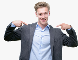 Young handsome blond business man looking confident with smile on face, pointing oneself with fingers proud and happy.