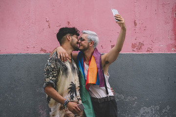 Gay couple of boys kissing with Smatphone in the city of Madrid