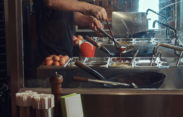 Cooking process in an Asian restaurant. Cook is stirring vegetables in wok.