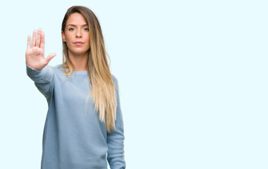 Beautiful young woman wearing sweater and jeans with open hand doing stop sign with serious and confident expression, defense gesture