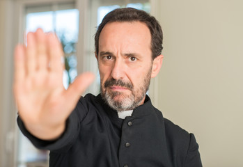 Christian priest man with open hand doing stop sign with serious and confident expression, defense gesture