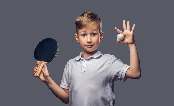 Redhead schoolboy dressed in a white t-shirt holds a ping-pong racquet and ball in a studio. Isolated on a gray background.