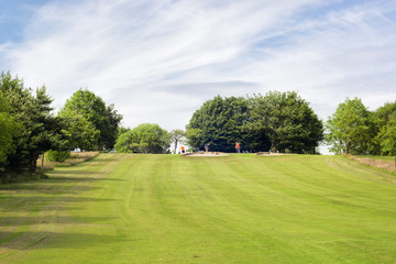 Golf field and three unrecognisable golf players at a distance
