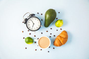 morning coffee in a white cup Croissant Avocado Awakening with an alarm clock Breakfast cheerfulness, a healthy breakfast freshness