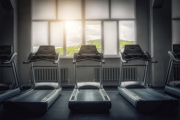 The interior of an empty gym with view of the picturesque mountains. Treadmill. The concept of a healthy lifestyle. Diet and fat burning. Sport and beauty.