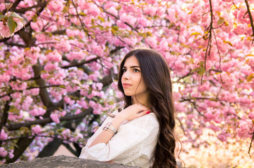 portrait of a young teenage girl looking at blooming sakura trees