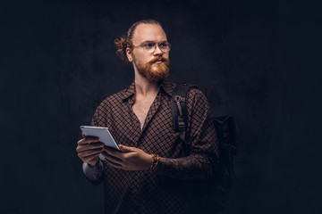 Portrait of a redhead hipster student in glasses dressed in a brown shirt, holds a backpack and digital tablet, posing at a studio. Isolated on a dark background.