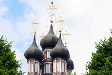 Domes of the Orthodox Church with Golden crosses against the blue cloudy sky