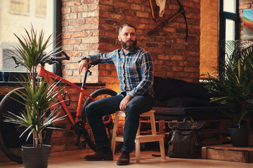 Handsome bearded hipster male in a blue fleece shirt and jeans sitting on a wooden stool at a studio with a loft interior.