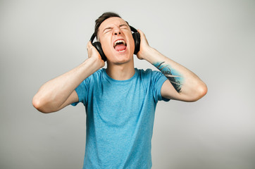 Young funny caucasian guy in blue t-shirt isolated listens to rock music on headphones on light gray background.
