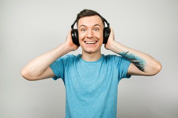 Young funny caucasian guy in blue t-shirt guy listens to music on headphones isolated on light gray background.