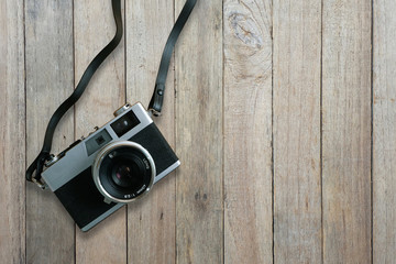 Old film camera on old wooden floor, top view with copy space