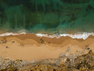Aerial view of sandy beach with waves. Drone photo