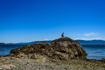 Woman in black pants and pink shirt climbing a rock formation on a beach in the San Juan Islands, the Salish Sea and other islands in the background, sunny day with a blue sky and while clouds