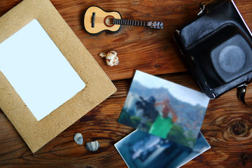 Camera, photos, toy guitar and seashells on wooden table. Summer vacation concept