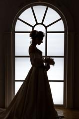 Beautiful bride stands silhouette near window
