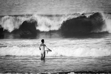 black and white sport surf picture with lonely surfer look a t a big waves in the background. wait the right time to enter in the dangerous water and have fun