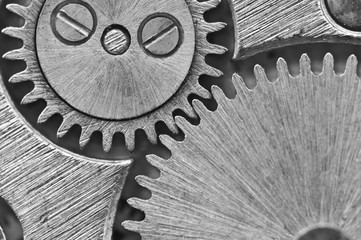 Macro. Black and white background.  Metal close-up background of an old clock mechanism of cogwheels. Conceptual photo for your successful business design or other successful variants