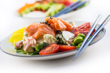 Japanese salad with fish salmon and vegetable and chopsticks