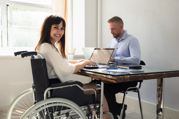 Happy Disabled Businesswoman Working On Laptop